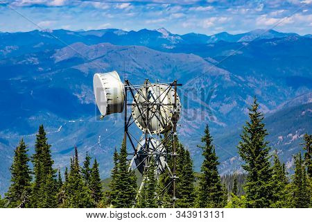 Juxtaposition of a cellular network tower emitting EMF radiation pollution in rural Canada with a scenic view of the Rocky Mountains and pine trees stock photo