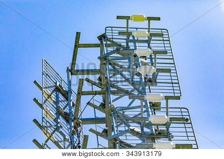 A low angle view of a cell site tower housing multiple antenna. Radio wave signal booster fixed to a steel pylon against a clear blue sky stock photo