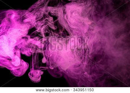 Abstract art pink colored smoke on black isolated background. Stop the movement of multicolored smoke on dark background stock photo