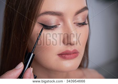 Make-up artist brush black eyeliner on the face of the woman. Young beautiful woman applying make-up by make-up artist stock photo