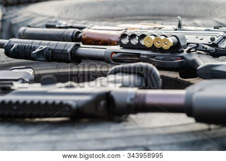 A shotgun with ammunition and automatic weapons lie on a car wheel. Concept of war, private military organizations stock photo