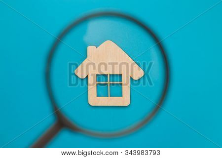 Magnifying glass looking at a small wooden house on a blue background. Mortgage and credit for the purchase. Real estate concept, buying affordable housing, real estate renting. Top view, flat lay stock photo
