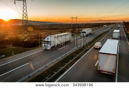 Convoys of White transportation trucks passing each other  on a highway. Highway transportation with white lorry tracks stock photo