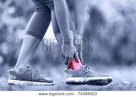 Broken twisted ankle - running sport injury. Female runner touching foot in pain due to sprained ank
