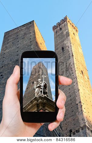 travel concept - tourist taking photo of saint petronius statue and two tower in Bologna on mobile gadget Italy stock photo