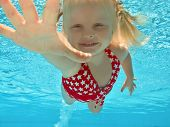 Child swimming submerged in pool