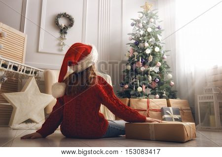 Merry Christmas and Happy Holidays! Cheerful cute little child girl with present. Kid holds a gift b