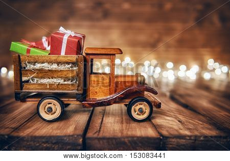 Merry Christmas and Happy Holidays! Gifts boxes presents on toy car and Christmas garland lights on