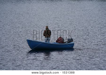 Men fishing in small boat on a lake ** Note: Slight blurriness, best at smaller sizes stock photo