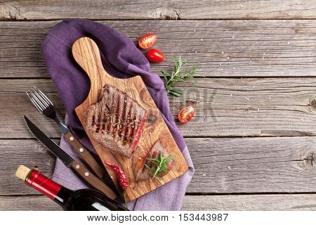Grilled beef steak with rosemary, salt and pepper and red wine on wooden table. Top view with copy space stock photo