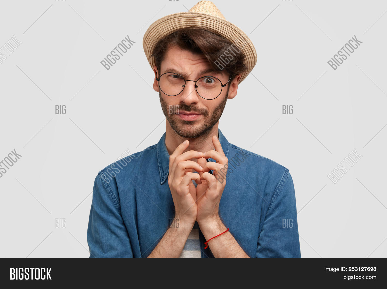 Attractive Bearded Male Keeps Hands Together And Looks With