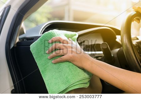 Woman worker cleaning car dashboard with Microfiber cloth,Car detailing stock photo