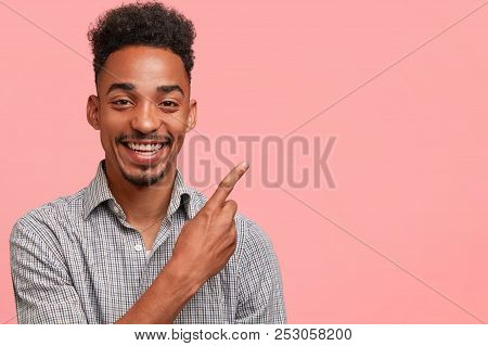 Portrait of black hipster guy with amazed expression, looks in bewilderment, being astonished with recent news, dressed in elegant checkered shirt, isolated on pink background. Surprisement and shock stock photo