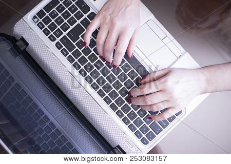 Secretary typist typing on laptop pc computer keyboard keys with hands with red nail varnish. stock photo