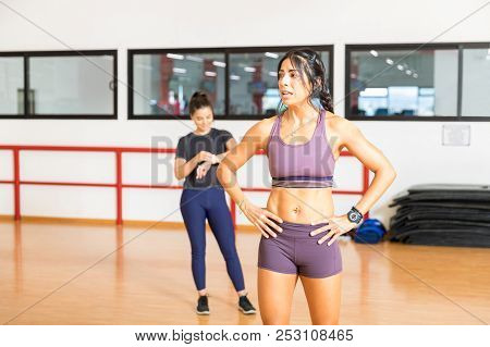 Exhausted mid adult woman standing with hands on hips after exercising in a gym class stock photo