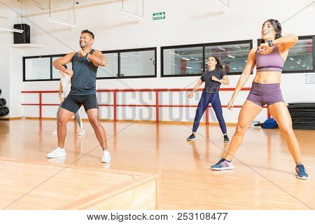 Excited male and female athletes working out and enjoying a dance class in a gym stock photo