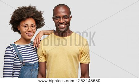 Vertical shot of stupefied African American male and female stare at camera with great surprisement, keep hands on cheeks, realize shocking news, pose against white background. Shock concept stock photo