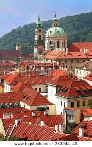 St Nicholas Church dome above red roof tops of Mala Strana and Petrin hill as backdrop in Prague, Czech Republic stock photo
