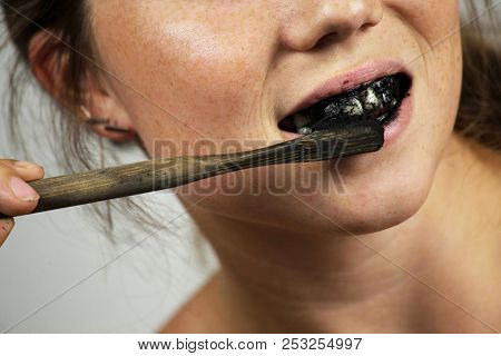 young woman brushing her teeth with a black tooth paste with active charcoal, and black tooth brush on white background for Teeth whitening clean stock photo