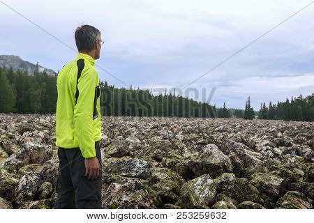 Man hiker on the stone river in Taganay National Park. stock photo