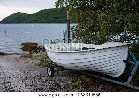 Small white rowing boat constructed in fibre glass to reflect traditional wooden vessels with its trailer on slipway by the sea stock photo