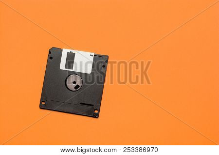 floppy data storage diskette on orange background with copy space stock photo