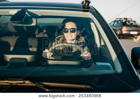 Portrait of a young smiling joyful woman or girl driver inside the car. Daily trips on transport or tourism, road travel or adventure. stock photo