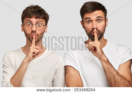 Two unhappy bearded young guys have displeased expressions, point with both index fingers above, show free space for your advertisement or promotional text, have sullen looks. Teamwork concept stock photo