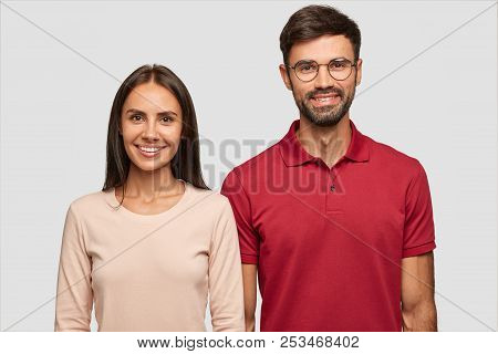 Lovely brunette young female with tanned skin, toothy smile, dark long hair, dressed in casual swetaer happy to spend free time in company of best friend, smile positively together, stand indoor stock photo