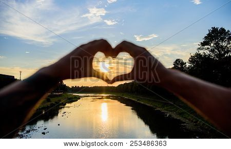 Summer memories concept. Top places for romantic date. Sunset sunlight romantic atmosphere. Male hands in heart shape gesture symbol of love and romance. Heart gesture in front of sunset above river stock photo