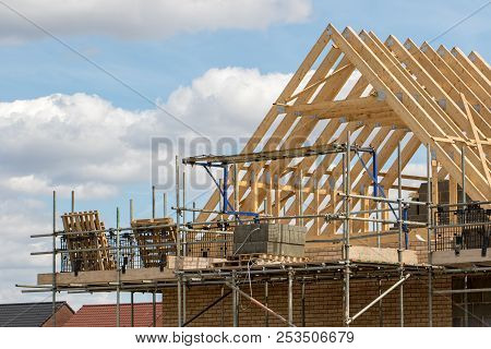 Construction industry. Timber framework of house roof trusses with scaffold on a building being built on a new housing estate. stock photo