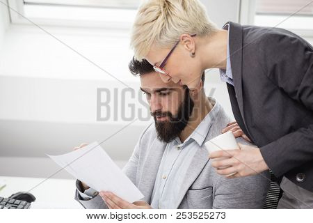 Group of young architects working in project biro looking at plans and discuss about projects while one of them holding cup of coffee on her hand stock photo