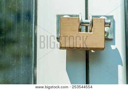 Padlock. Locked golden modern steel safety or security padlock on the entrance doors close up stock photo