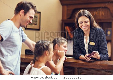Happy family checking in hotel at reception desk stock photo