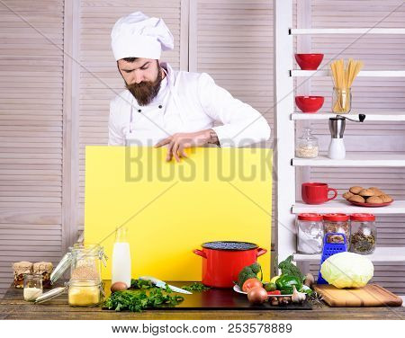 Bearded chef holds board for text. Chef looking on board for advertising. Chef on kitchen. Food service. Cuisine. Healthy food cooking. Culinary concept. Man in white cook uniform. Cooking. stock photo