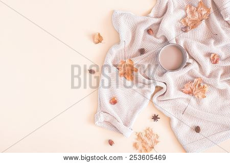 Autumn cozy composition. Cup of coffee, women fashion sweater, dried leaves on pastel beige background. Autumn, fall concept. Flat lay, top view, copy space stock photo
