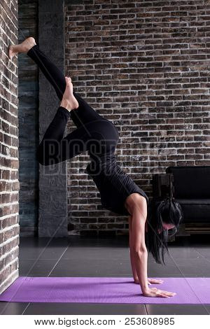 Beginning female yogi practicing yoga inversion poses standing on hands upside down leaning against wall in fitness club stock photo