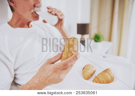 Close up. Old Man Having Breakfast in Bed at Home. Morning Routine. Resting at Home. White Bed. Breakfast at Morning. Elder Person in Bed. Croissant with Glass of Milk. Healthy Food. stock photo