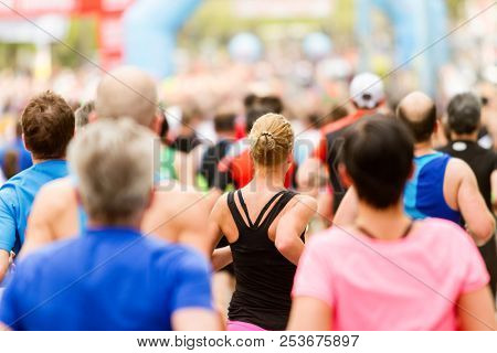 Running Crowd At The Marathon. Many Runners Passing The Start Or Finish Line. Woman In Focus.