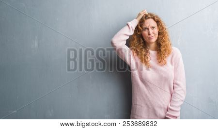 Young redhead woman over grey grunge wall wearing pink sweater confuse and wonder about question. Un
