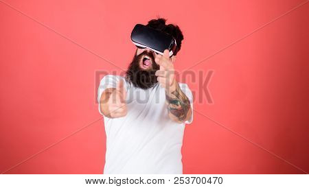 Shooting gallery VR. Man bearded hipster with virtual reality headset on red background. First person shooter shows how addictive VR could be. Man hand gesture as gun play shooter game in VR glasses stock photo