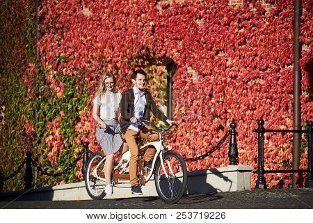 Young happy tourist couple, handsome bearded man and pretty long-haired blond woman cycling tandem bicycle on bright sunny day on background of building fully overgrown with red ivy leaves. stock photo