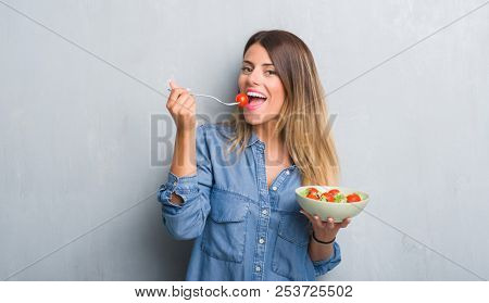 Young adult woman over grey grunge wall eating healthy tomato salad with a happy face standing and s