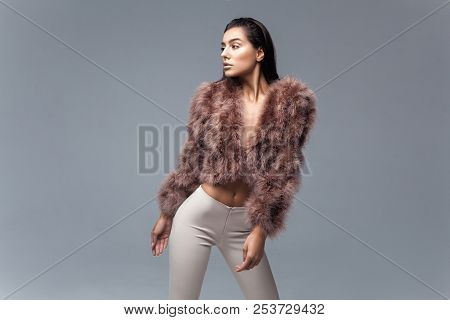 Young elegant girl posing in fluffy pink cape with artificial fur and beige flare trousers on gray background. Fashion retro style stock photo