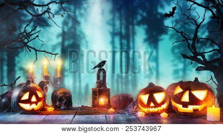 Scary horror background with halloween pumpkins jack o lantern, placed on wooden deck. Halloween spo