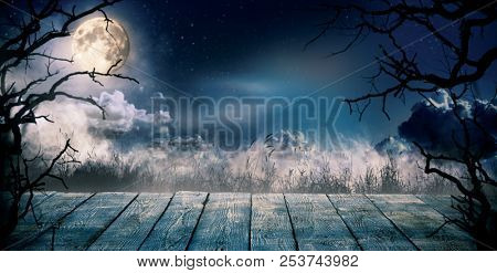 Scary horror background with empty wooden deck, ready for product placement. Halloween spooky backgr
