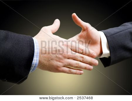 Business handshake on yellow and black colored background stock photo