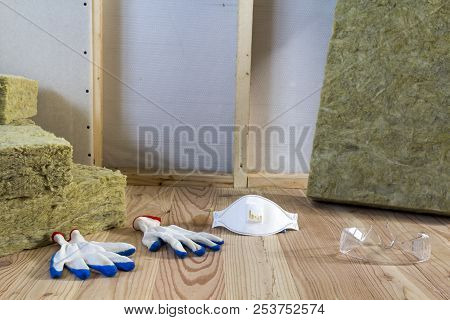 Rock wool and fiberglass insulation staff material for cold barrier. Tools for work with glass wool: protective goggles, glasses and mask. Warm home, economy, construction and renovation concept. stock photo