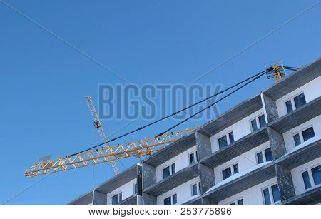 Construction site with cranes on sky background. The Builder works on the roof of a multi-storey building. stock photo