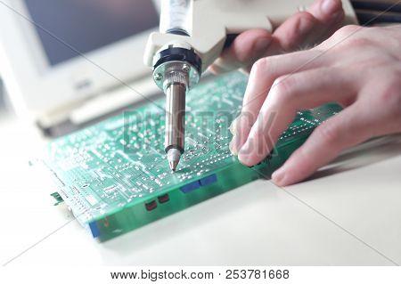 Technician repair circuit board with Electric Vacuum Solder Sucker Desoldering Pump stock photo